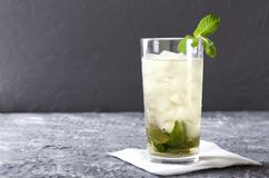 Glass of mint julep served on the napkin.Grey bar table against gray wall.Empty space for your design stock images