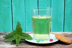 Glass of mint tea and cookie. Glass of mint tea with turquoise background and text space Royalty Free Stock Photo