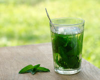 А glass of mint tea on a wooden table Stock Photography