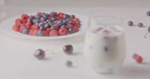 Changing focus from a plate with sweet ripe raspberry blueberry, cherry on a glass with berries and milk on white table. A glass with mix berries and milk. A stock video footage