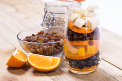 Glass of mixed fresh fruits and raisins. Glass of mixed fresh exotic fruits and raisins for on the wooden table Stock Photos