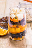 Glass of mixed fresh fruits and raisins. Glass of mixed fresh exotic fruits and raisins for on the wooden table Stock Photo