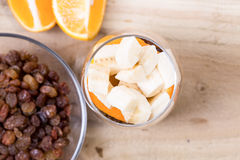 Glass of mixed fresh fruits and raisins. Glass of mixed fresh exotic fruits and raisins for on the wooden table Stock Image