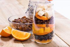 Glass of mixed fresh fruits and raisins. Glass of mixed fresh exotic fruits and raisins for on the wooden table Stock Images