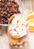 Glass of mixed fresh fruits and raisins. Glass of mixed fresh exotic fruits and raisins for on the wooden table Royalty Free Stock Photo