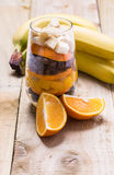 Glass of mixed fresh fruits and raisins. Glass of mixed fresh exotic fruits and raisins for on the wooden table Royalty Free Stock Images