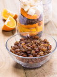 Glass of mixed fresh fruits and raisins. Glass of mixed fresh exotic fruits and raisins for on the wooden table Royalty Free Stock Photography