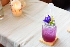 A glass of mixed juice with lemon and pea flowers. Stock Photo
