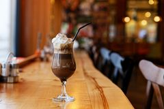 Glass of mocha with a cap of whipped cream on a table in a cafe. Glass of chocolate mocha with a cap of whipped cream and straw on a table in a cafe. Shallow royalty free stock photo