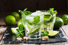 Glass of mojito cocktail with fresh lime. And mint on a black stone board Stock Photo