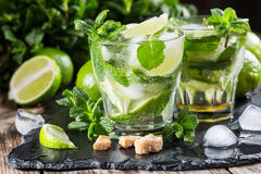 Glass of mojito cocktail with fresh lime. And mint on a black stone board Stock Photos