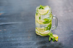 Glass of mojito with lime and mint ice cube close-up on dark wood background Royalty Free Stock Images