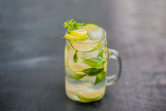 Glass of mojito with lime and mint ice cube close-up on dark wood background Royalty Free Stock Photo