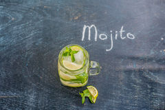 Glass of mojito with lime and mint ice cube close-up on dark wood background Stock Photos
