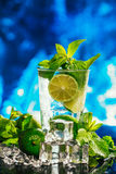 Glass of mojito with lime and mint ice cube close-up red straw on blue background Royalty Free Stock Images
