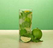 Glass of a mojito, spearmint leaf and juicy lime Royalty Free Stock Image