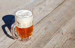 Glass mug with beer standing on the table outdoor. On sunny summer day Royalty Free Stock Image