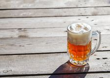Glass mug with beer standing on the table outdoor. On sunny summer day Royalty Free Stock Photos