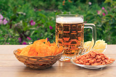 Glass mug of beer on wooden table with potato chips in wicker ba Stock Images