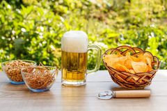 Glass mug of beer on wooden table with potato chips in wicker ba Stock Photo