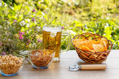 Glass mug of beer on wooden table with potato chips in wicker ba Royalty Free Stock Photos