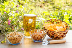 Glass mug of beer on wooden table with potato chips in wicker ba Stock Image