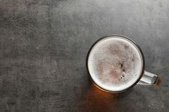 Glass mug with cold tasty beer. On grunge background, top view stock image