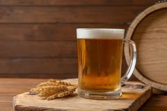 Glass mug with cold tasty beer and malt. On wooden table Royalty Free Stock Photo
