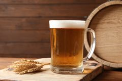 Glass mug with cold tasty beer and malt. On wooden table stock photos