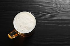 Glass mug with cold tasty beer. On wooden background, view from above royalty free stock photography