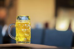 Glass mug of golden light beer in bar, in pub close up. Real scene. Beer culture, Craft brewery, uniqueness of beer. Glass mug of golden light beer in bar or in Royalty Free Stock Photos