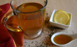 Glass mug of green tea with lemon and honey. Mug of hot tea with lemon slices and honey on a wood problme Stock Photos