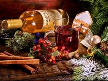 Glass mug of grog lying next to red wine bottle . Stock Images