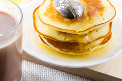 Glass mug of hot cocoa and pancakes with honey Royalty Free Stock Image