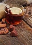 Glass mug of hot drink with a lemon and cinnamon Stock Photography