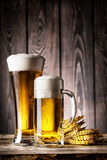 Glass and a mug of light beer with foam and ears Stock Image