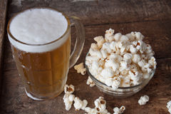 Glass mug of light beer with popcorn on wooden table, close up Stock Image