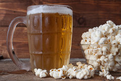 Glass mug of light beer with popcorn on wooden table, close up Royalty Free Stock Photography