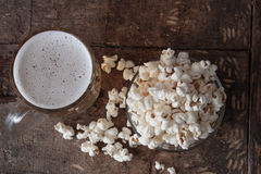 Glass mug of light beer with popcorn on wooden table, close up Royalty Free Stock Image
