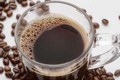 Glass mug with strong drink. Made of the arabica sort. Coffee beans are scattered on the white surface. Isolated stock photos