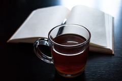 A glass mug with tea and a lemon slice, notebook with blank pages, black pen on dark desk Royalty Free Stock Images