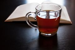 A glass mug with tea and a lemon slice, notebook with blank pages, black pen on dark desk Royalty Free Stock Photography
