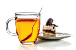 Glass mug of tea and a piece of cake on a saucer royalty free stock images