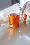 Glass mug with tea, teapot en teabag on table Royalty Free Stock Photo