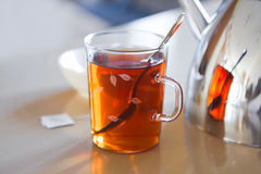 Glass mug with tea, teapot en teabag on table Royalty Free Stock Image