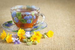 Glass mug of tea with yellow and blue flowers. Full glass mug of tea with yellow and blue flowers Royalty Free Stock Images