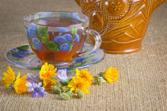 Glass mug of tea with yellow and blue flowers. Full glass mug of tea with yellow and blue flowers Royalty Free Stock Photography