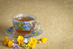 Glass mug of tea with yellow and blue flowers. Full glass mug of tea with yellow and blue flowers Stock Images