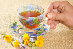 Glass mug of tea with yellow and blue flowers. Full glass mug of tea with yellow and blue flowers Stock Photography