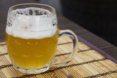 Glass mug of unfiltered weizen beer on table. One glass mug of unfiltered craft draft white wheat weizen beer on wooden bamboo mat on table, close up Royalty Free Stock Photos